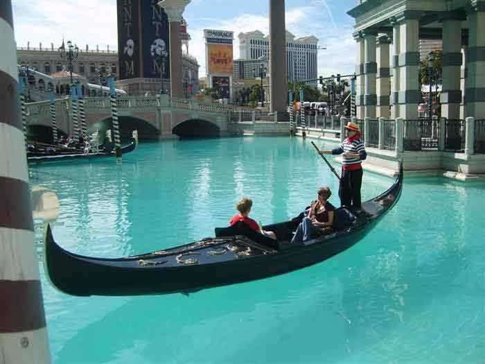 People inside a gondola and a singing gondolier at the Venetian Hotel in Las Vegas